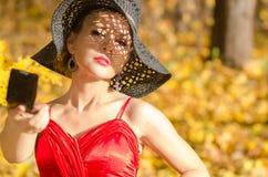 Πορτρέτο κινηματογραφήσεων σε πρώτο πλάνο θηλυκού καυκάσιου, με το σχέδιο σκιών από το καπέλο στο πρόσωπο που κρατά έναν καθρέφτη Στοκ φωτογραφία με δικαίωμα ελεύθερης χρήσης