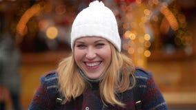 Πορτρέτο κινηματογραφήσεων σε πρώτο πλάνο μιας όμορφης χαμογελώντας νέας γυναίκας που φορά το θερμό ιματισμό Κορίτσι που γελά και απόθεμα βίντεο