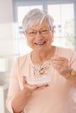Πορτρέτο κινηματογραφήσεων σε πρώτο πλάνο της ευτυχούς γυναίκας που τρώει τα δημητριακά Στοκ Εικόνες