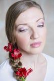 Πορτρέτο κινηματογραφήσεων σε πρώτο πλάνο της νέας όμορφης μοντέρνης γυναίκας με τα πανέμορφα λουλούδια κόκκινων ελατηρίων στοκ φωτογραφία