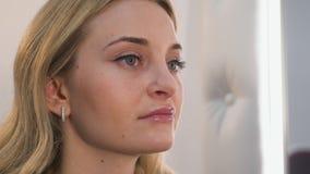 Πορτρέτο κινηματογραφήσεων σε πρώτο πλάνο της όμορφης ξανθής γυναίκας που κάνει τη σύνθεση στα χείλια της απόθεμα βίντεο