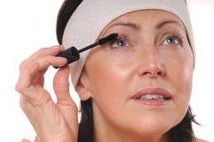 Πορτρέτο κινηματογραφήσεων σε πρώτο πλάνο της ώριμης γυναίκας που εφαρμόζει mascara στα eyelashes Στοκ Φωτογραφίες