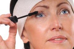 Πορτρέτο κινηματογραφήσεων σε πρώτο πλάνο της ώριμης γυναίκας που εφαρμόζει mascara στα eyelashes Στοκ φωτογραφία με δικαίωμα ελεύθερης χρήσης
