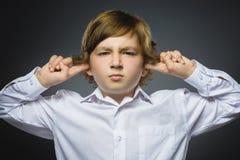 Πορτρέτο κινηματογραφήσεων σε πρώτο πλάνο του ανησυχημένου αγοριού που καλύπτει τα αυτιά της, παρατήρηση μην ακούστε τίποτα Ανθρώ στοκ εικόνα