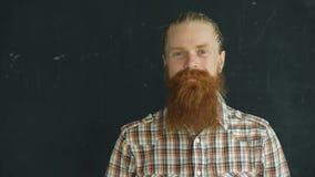 Πορτρέτο κινηματογραφήσεων σε πρώτο πλάνο του ατόμου hipster που εξετάζει τη κάμερα και που χαμογελά στο μαύρο υπόβαθρο απόθεμα βίντεο