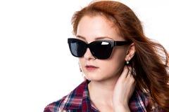 Πορτρέτο κινηματογραφήσεων σε πρώτο πλάνο του κοκκινομάλλους κοριτσιού με τα γυαλιά ηλίου που κοιτάζουν Στοκ Εικόνες