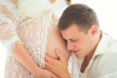 Πορτρέτο κινηματογραφήσεων σε πρώτο πλάνο του μελλοντικού πατέρα, της έγκυου κοιλιάς αγκαλιάσματος και ακούσματος Στοκ Φωτογραφία