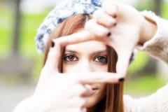 Πορτρέτο κινηματογραφήσεων σε πρώτο πλάνο του νέου κοριτσιού που κάνει το πλαίσιο με τα χέρια της. Στοκ εικόνα με δικαίωμα ελεύθερης χρήσης