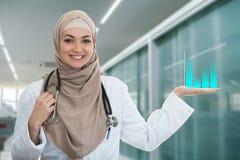 Πορτρέτο κινηματογραφήσεων σε πρώτο πλάνο του φιλικού, χαμογελώντας βέβαιου μουσουλμανικού θηλυκού γιατρού που κρατά τα ιατρικά σ Στοκ φωτογραφία με δικαίωμα ελεύθερης χρήσης