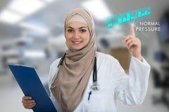 Πορτρέτο κινηματογραφήσεων σε πρώτο πλάνο του φιλικού, χαμογελώντας βέβαιου μουσουλμανικού θηλυκού γιατρού που κρατά τα ιατρικά σ Στοκ εικόνες με δικαίωμα ελεύθερης χρήσης
