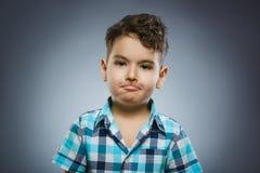 Πορτρέτο κινηματογραφήσεων σε πρώτο πλάνο του όμορφου αγοριού με την έκπληκτη έκφραση στο γκρίζο υπόβαθρο στοκ φωτογραφία