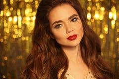 Πορτρέτο κοριτσιών ομορφιάς μόδας που απομονώνεται στο χρυσό υπόβαθρο φω'των Χριστουγέννων ακτινοβολώντας bokeh Γοητεία makeup Μα στοκ εικόνες