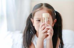 Πορτρέτο λίγου ασιατικού κοριτσιού που εξετάζει διαθέσιμο να βρεθεί κλεψυδρών στο κρεβάτι στο σπίτι Αναμονής χρόνος με τα sandgla στοκ φωτογραφία