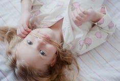Πορτρέτο λίγου ξανθού κοριτσιού στις ρόδινες πυτζάμες που κάνει mustache από την τρίχα και το χαμόγελό της Στοκ εικόνα με δικαίωμα ελεύθερης χρήσης