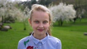 Πορτρέτο λίγο καυκάσιο κορίτσι με τα μπλε μάτια στο όμορφο πουκάμισο που στέκεται στο πάρκο στην άνοιξη απόθεμα βίντεο
