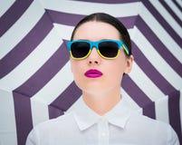Πορτρέτο μιας αρκετά νέας γυναίκας στα ζωηρόχρωμα γυαλιά ηλίου Στοκ Εικόνες