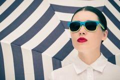 Πορτρέτο μιας αρκετά νέας γυναίκας στα ζωηρόχρωμα γυαλιά ηλίου Στοκ Φωτογραφίες