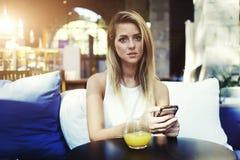 Πορτρέτο μιας γοητευτικής γυναίκας που χρησιμοποιεί το κινητό τηλέφωνο κατά τη διάρκεια του προγεύματος στο εσωτερικό καφετεριών  Στοκ Φωτογραφίες