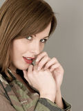 Πορτρέτο μιας γυναίκας ένα στρατιωτικό σακάκι κάλυψης που φαίνεται ντροπαλό και Στοκ εικόνα με δικαίωμα ελεύθερης χρήσης