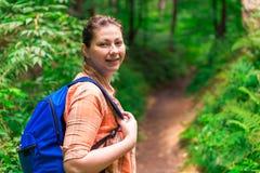 Πορτρέτο μιας γυναίκας με ένα σακίδιο πλάτης σε ένα πράσινο δάσος Στοκ Εικόνες