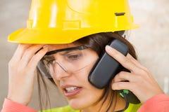 Πορτρέτο μιας γυναίκας με το κράνος ασφάλειας και το κινητό τηλέφωνο στοκ εικόνες