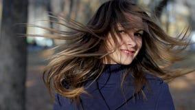 Πορτρέτο μιας γυναίκας που γυρίζει την επικεφαλής σε αργή κίνηση 4k 60fps Κορίτσι σε ένα παλτό που περπατά στο πάρκο πόλεων φθινο απόθεμα βίντεο
