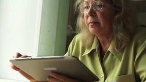 Πορτρέτο μιας γυναίκας στην ηλικία με το PC ταμπλετών