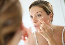 Πορτρέτο μιας γυναίκας στον καθρέφτη που εφαρμόζει μια κρέμα στοκ φωτογραφία με δικαίωμα ελεύθερης χρήσης