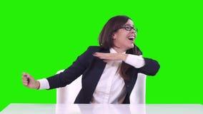 Πορτρέτο μιας γυναίκας στο γραφείο σε ένα πράσινο υπόβαθρο Το brunette στα γυαλιά χαίρεται, χαμογελά και χορεύει στην εργασία απόθεμα βίντεο