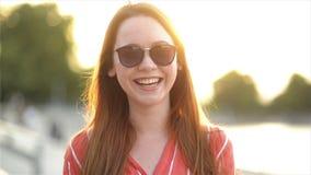 Πορτρέτο μιας ελκυστικής νέας γυναίκας που εξετάζει δεξιά τη κάμερα που χαμογελά και που γελά Κλείστε επάνω την άποψη του κοριτσι φιλμ μικρού μήκους
