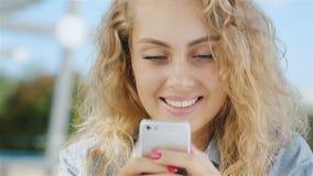 Πορτρέτο μιας ελκυστικής νέας γυναίκας που εξετάζει την τηλεφωνική οθόνη: χαμόγελο απόθεμα βίντεο