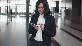 Πορτρέτο μιας επιχειρησιακής γυναίκας με ένα τηλέφωνο στα χέρια της νέα γυναίκα στο λόμπι ενός κτιρίου γραφείων απόθεμα βίντεο