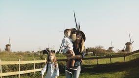Πορτρέτο μιας ευρωπαϊκής οικογένειας κοντά στο αγρόκτημα ανεμόμυλων Όμορφη γυναίκα στο καπέλο με τον περίπατο μικρών παιδιών και  απόθεμα βίντεο