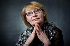 Πορτρέτο μιας ευτυχούς ανώτερης γυναίκας που χαμογελά στη κάμερα Πέρα από τη μαύρη ανασκόπηση Στοκ εικόνα με δικαίωμα ελεύθερης χρήσης