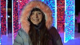 Πορτρέτο μιας ευτυχούς γυναίκας δίπλα στα φω'τα στην οδό το βράδυ απόθεμα βίντεο