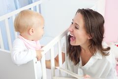 Πορτρέτο μιας ευτυχούς μητέρας που γελά με το χαριτωμένο μωρό στο παχνί Στοκ Εικόνα