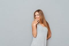 Πορτρέτο μιας ευτυχούς νέας γυναίκας που καλύπτει το στόμα της Στοκ εικόνες με δικαίωμα ελεύθερης χρήσης