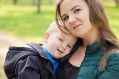 Πορτρέτο μιας ευτυχούς νέας μητέρας που κρατά έναν χαμογελώντας γιο στοκ φωτογραφία με δικαίωμα ελεύθερης χρήσης