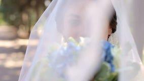 Πορτρέτο μιας ευτυχούς νύφης με μια ανθοδέσμη των άσπρων και μπλε λουλουδιών στο πάρκο φιλμ μικρού μήκους