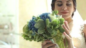 Πορτρέτο μιας ευτυχούς νύφης με μια ανθοδέσμη των άσπρων και μπλε λουλουδιών, κινηματογράφηση σε πρώτο πλάνο φιλμ μικρού μήκους