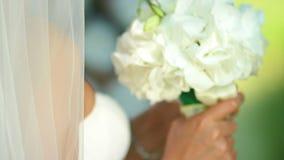 Πορτρέτο μιας ευτυχούς νύφης Μια όμορφη νύφη σε ένα πέπλο κρατά μια ανθοδέσμη των λουλουδιών φιλμ μικρού μήκους