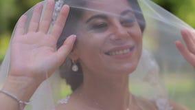 Πορτρέτο μιας ευτυχούς νύφης σε ένα πέπλο με ένα καλυμμένο κεφάλι σε ένα θερινό πάρκο απόθεμα βίντεο