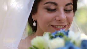 Πορτρέτο μιας ευτυχούς νύφης σε ένα πέπλο με ένα καλυμμένο κεφάλι με τα λουλούδια φιλμ μικρού μήκους
