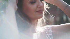 Πορτρέτο μιας ευτυχούς νύφης στο άσπρο φόρεμα στο πάρκο, κινηματογράφηση σε πρώτο πλάνο φιλμ μικρού μήκους