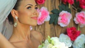Πορτρέτο μιας ευτυχούς νύφης όμορφη νύφη στο πέπλο με μια ανθοδέσμη στα χέρια στα πλαίσια ενός ξύλινου τοίχου με φιλμ μικρού μήκους