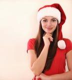 Πορτρέτο μιας ελκυστικής γυναίκας στο καπέλο Santa που ονειρεύεται για τις διακοπές Χριστουγέννων Στοκ Εικόνες