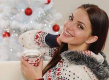 Πορτρέτο μιας ελκυστικής νέας γυναίκας που απολαμβάνει το ζεστό ποτό σε Chri Στοκ Φωτογραφίες