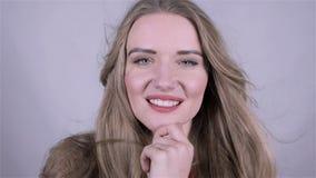 Πορτρέτο μιας ελκυστικής χαμογελώντας ξανθής γυναίκας που απομονώνεται στο γκρίζο υπόβαθρο απόθεμα βίντεο