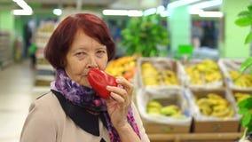 Πορτρέτο μιας ηλικιωμένης γυναίκας ογδόντα ετών στην υπεραγορά με το πιπέρι διαθέσιμο φιλμ μικρού μήκους