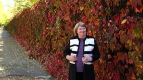 Πορτρέτο μιας ηλικιωμένης γυναίκας στο πάρκο φθινοπώρου ενάντια στα κόκκινα δέντρα 4K απόθεμα βίντεο